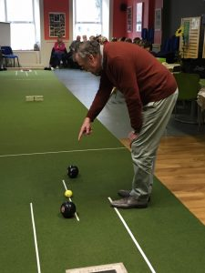 man showing how to play indoor bowls in Cumann na Daoine main hall